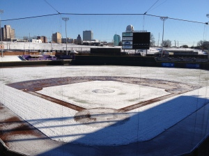 Seeing snow at a baseball field is always strange.